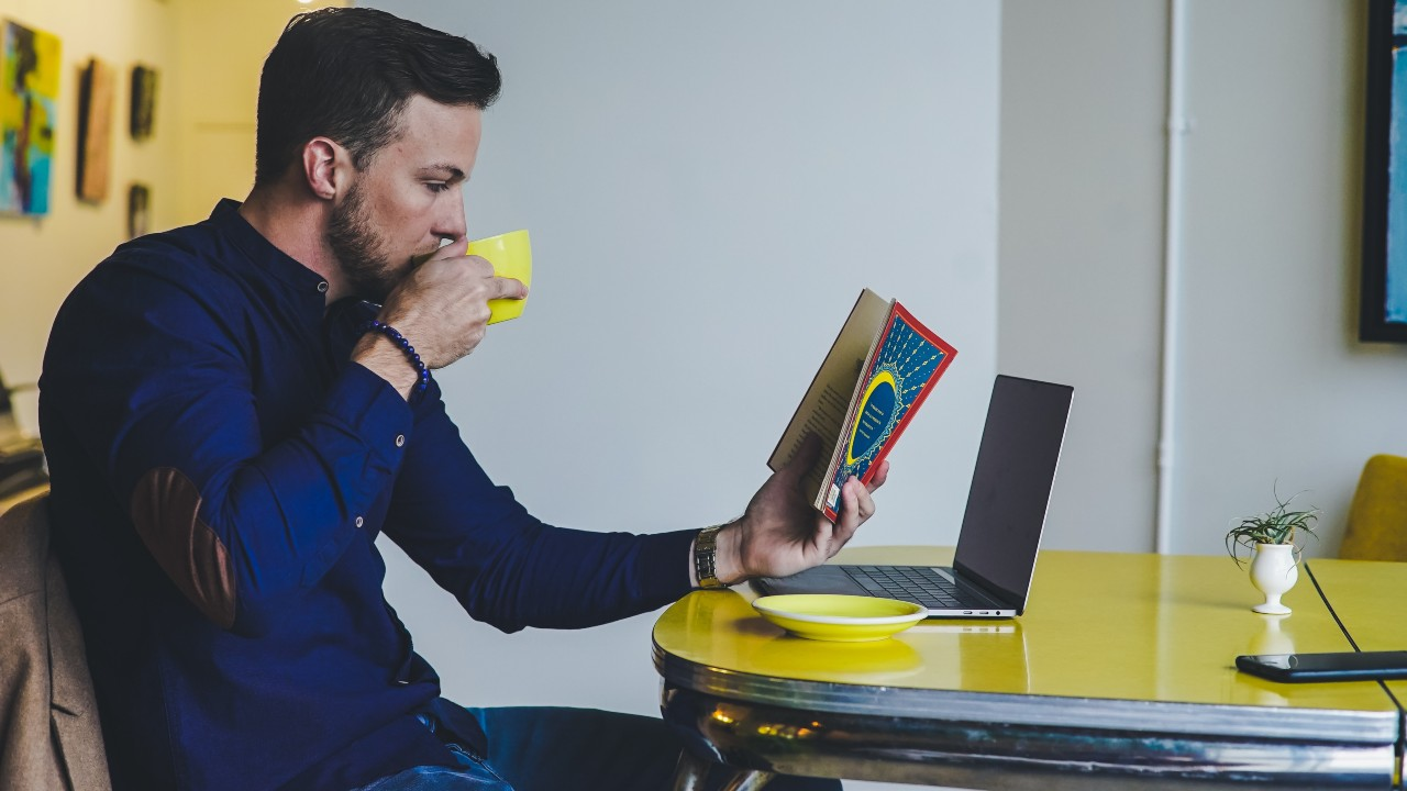 Man reading book and computer