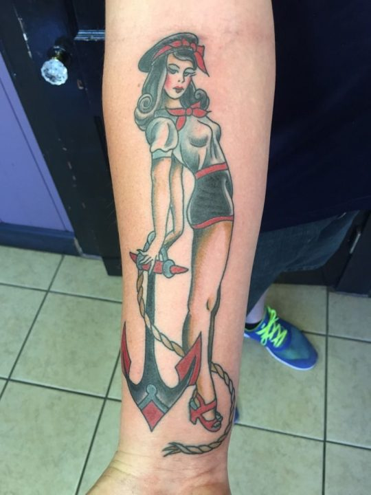 sailor pinup girl tattoo with anchor on forearm